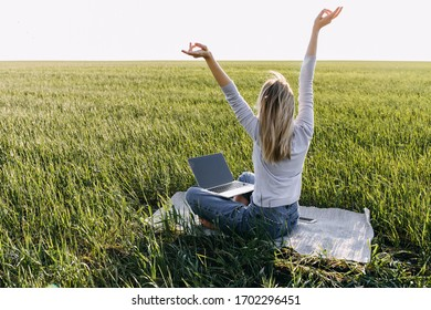 Young woman with a laptop working in nature, field with fresh green grass, in sun light. Freelancer worker concept.