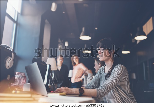 Young woman with laptop at workplace. Group of young business people working together. Big open space office. Four persons. Intentional lens flares