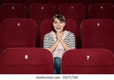 Young woman laughing in the movie theater