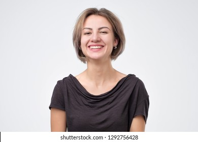 Young woman laughing on gray background on funny joke of her boyfriend.