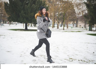 young woman laughing outdoor in park and playing with snowball – cheerful, dynamic, youth