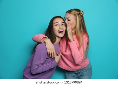 Young woman laughing while her friend whispering something funny against color background