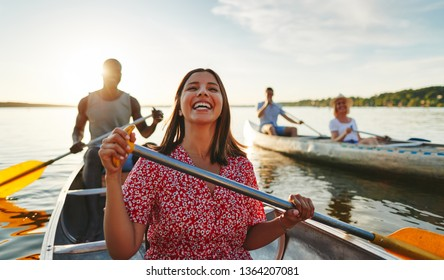 Young woman laughing while paddling a canoe with her boyfriend on a lake with another couple on a sunny summer afternoon