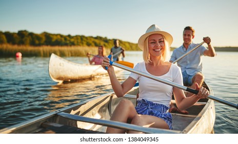Young woman laughing while paddling a canoe on a scenic lake with a group of friends on a sunny summer afternoon