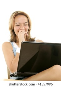 Young woman laughing while using her laptop