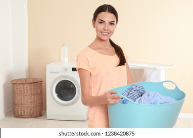 Young woman with laundry basket near washing machine at home. Space for text
