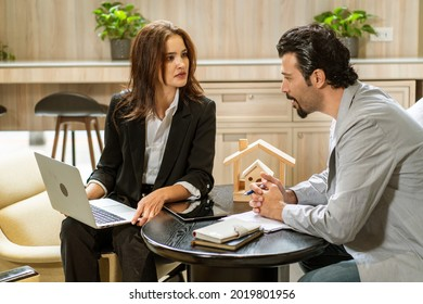 young woman lawyer in a suit holds a laptop and a handsome male client consults for a home loan in an agency looking at the real estate business.