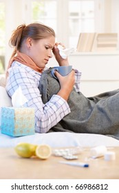 Young woman laying in bed, caught cold, feeling bad, drinking tea, taking vitamins.?