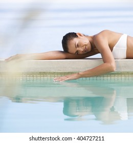 A young woman laying by a pool