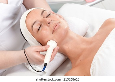 Young woman laying eyes closed, receiving facial beauty treatment in beauty saloon.