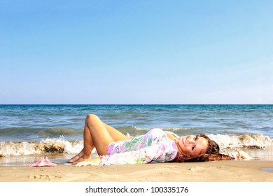 Young woman laying on a beach and enjoying the sun