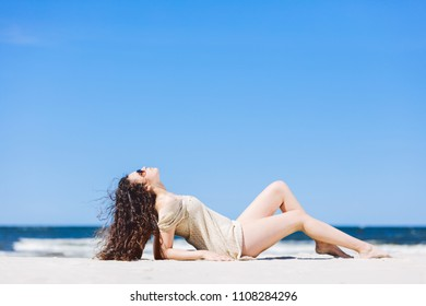 Young woman laying on the beach, sunbathing. Summer outdoor relax.