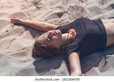 young woman laying on the beach with closed eyes