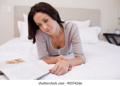 Young woman laying on the bed reading a magazine