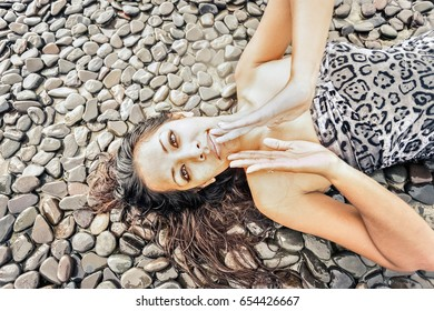 Young woman laying on a black gravel and looking up with her hands closed to each other