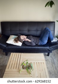 Young woman laying on a couch and talking on the phone