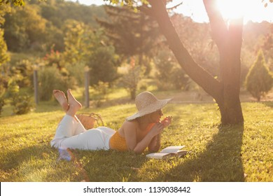 Young woman laying on grass and reading a book