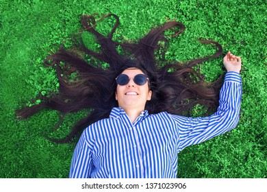 Young woman laying on green grass