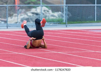 A young woman laying on the ground is stretching her legs after running