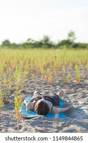 young woman laying on sand in a relaxing pose