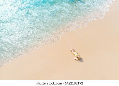 Young woman laying on sand beach