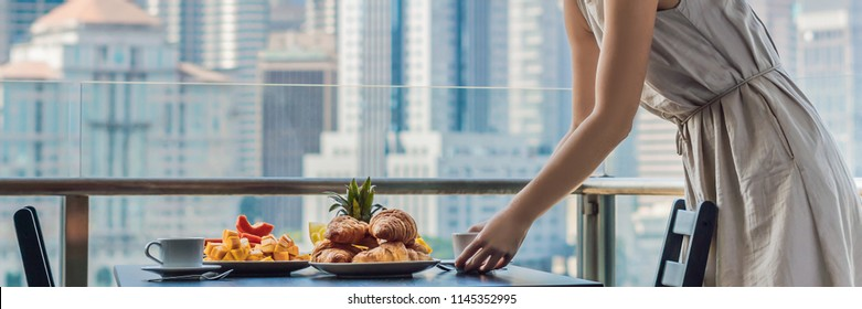 Young woman is laying on a table. Breakfast table with coffee fruit and bread croisant on a balcony against the backdrop of the big city BANNER, long format