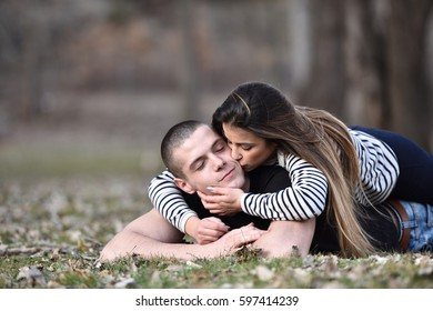Young woman laying on top of her boyfriend and kissing him in chick , romantic couple in love laying in grass outdoor