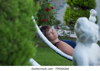 Young woman laying and relaxing on a white hammock in a garden with statues and roses.