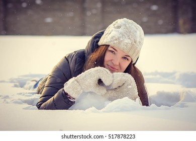 Young woman is laying in snow