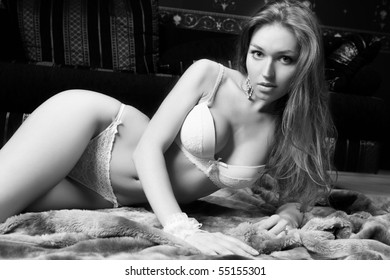 The young woman lays on fur. Black and white photo.
