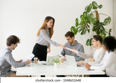 Young woman leader boss giving team members documents for review or consideration, smiling businesswoman presenting partners new project plan on approval or work results in report at group meeting