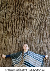 Young woman leaned her back against the trunk of a large tree. Closed eyes. Unity with nature