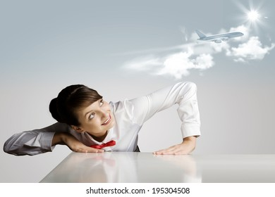 Young woman leaning above table and looking at airplane in sky