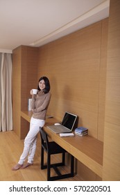 Young woman leaning against desk holding coffee