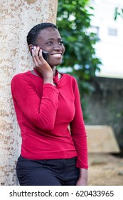 Young woman leaning against a tree, smiling on the phone.