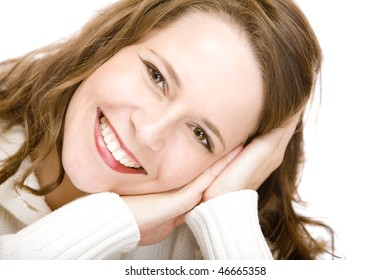 Young woman leaning cheek on hands and smiles happy  into camera. Isolated on white.