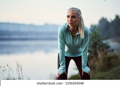 Young woman leaning on her knees during morning running exercise in park
