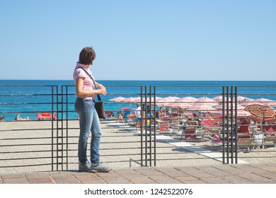 Young woman leaning on the railing observes the beach and the sea