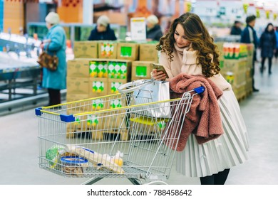 Young woman leaning on shopping cart in supermaket and using mobile phone