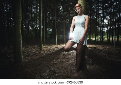Young woman leaning on a tree in a forest while holding a knife