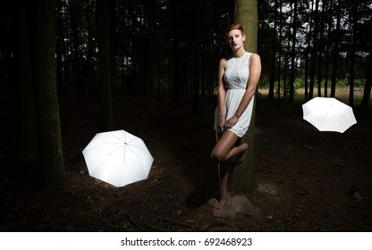 Young woman leaning on a tree in a forest, surrounded by white umbrellas