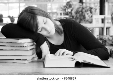 A young woman leans her head on a pile of books while studying.