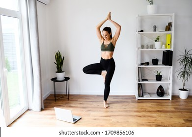 Young woman learn yoga from video tutorials. She looks at the laptop screen and repeats exercises