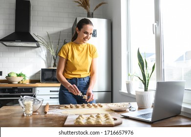 A young woman learns to cook, she watches video recipes on a laptop in the kitchen and cook a dish from the dough. Cooking at home concept