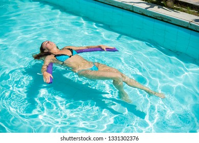 A young woman learns to swim in an outdoor pool using a swimming noodle.