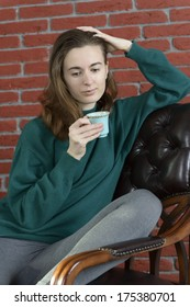 Young woman in a leather armchair with a cup against the red brick wall