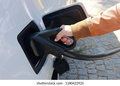 young woman with a leather jacket charging a white electric car