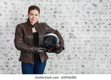 Young woman in leather protective clothes holding motorcycle helmet in hands, copyspace with brick wall of garage
