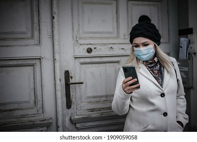 Young woman leaving house in winter, reading messages and wearing face mask due to covid-19 pandemic