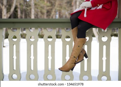 Young woman legs with boots at terrace boundary